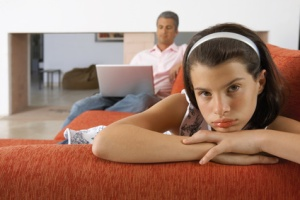 Girl lying down on a sofa, father working on the laptop.